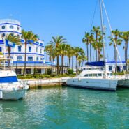 Boats and beautiful lighthouse building in Estepona port on Costa del Sol coast, Spain